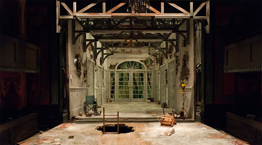 Dr. Faustus stage set is a derelict room with a hole in the floor and books strewn about