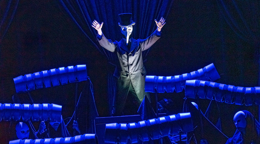 Man in white, beaked mask with arms upraised and surrounded by blue light