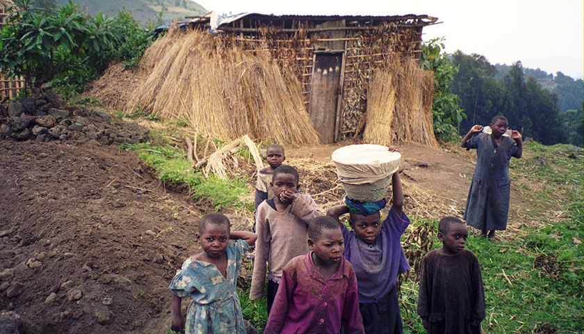 Children walking, one balancing cloth-wrapped container ion her head, with thatched building behind them
