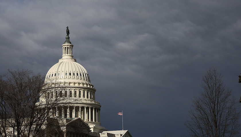 Capitol dome shines against dark clouds