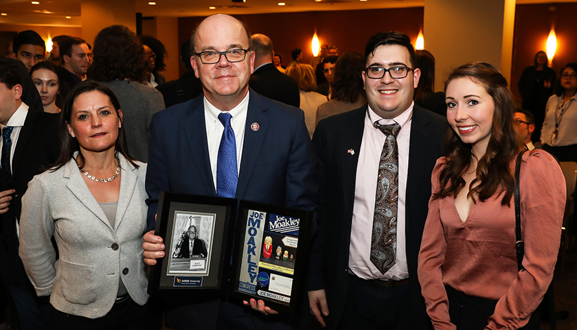 Congressman Jim McGovern holds gift from Suffolk group