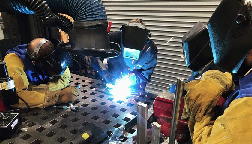 Three people in protective helmets and face coverings welding