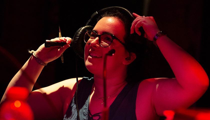 Aisling Mehigan putting on headphones and bathed in red light