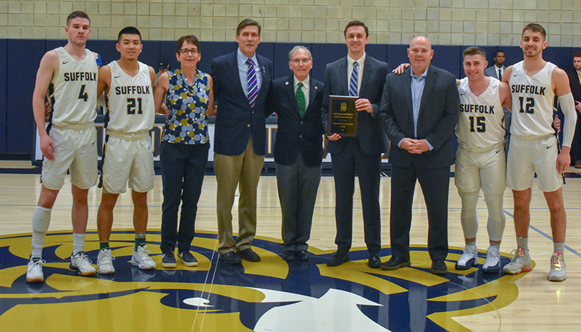 Jeff Juron holds plaque as group of officials and players pose at midcourt