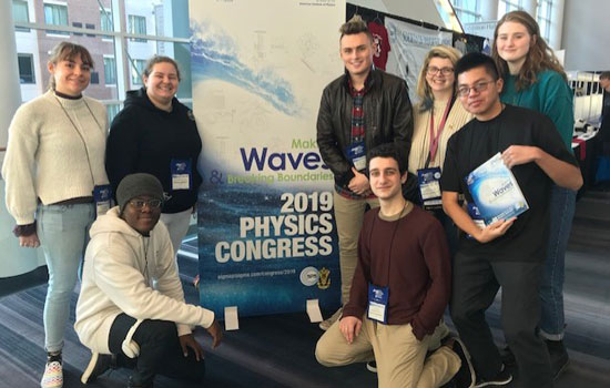 Students pose with poster at a physics research conference