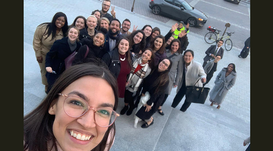 Congresswoman Alexandria Ocasio-Cortez in foreground as she takes selfie with Suffolk group