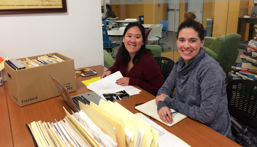 Two women with boxes of files at table in university archive