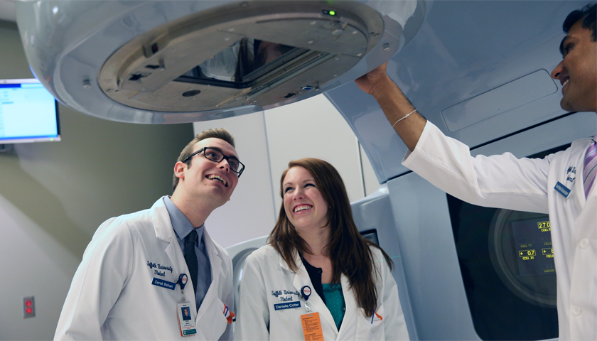 Three people in white lab coats set radiation equipment in place