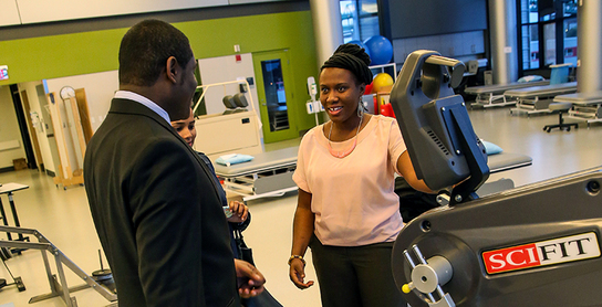 a student and faculty in physical therapy center, a student at health fitness center