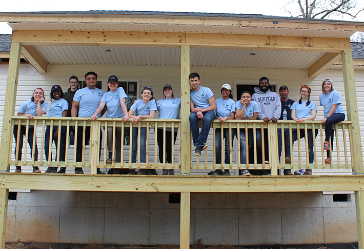 Some Suffolk students who participated in a University-sponsored Habitat for Humanity Alternative Spring Break trip pose for a group photo