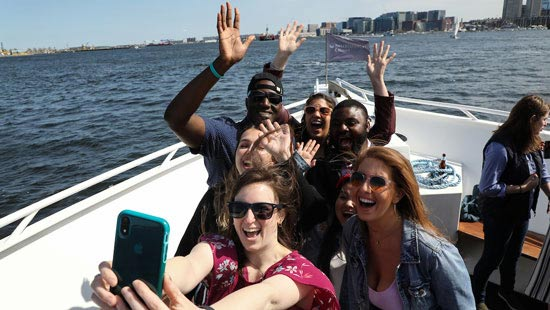 Students on a Boston Harbor boating trip take a selfie